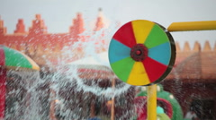 Multicolored spinning water wheel with splashes around poolside Stock Footage