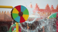 Colorful rotating water wheel with splashes is in aquapark in hotel area - stock footage
