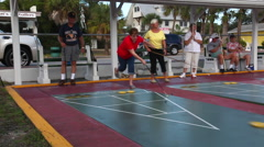 Senior citizens playing competitive shuffleboard game in Flager Ave in New Sm Stock Footage