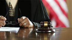 Judge's hand banging a gavel in a courtroom Stock Footage