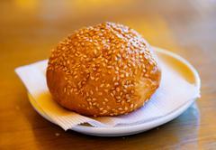 Golden fresh bun with sesame seeds on white plate with napkin - stock photo