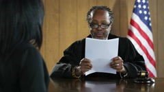Black male judge reading a verdict to black woman in court Arkistovideo