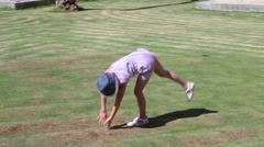 Stock Video Footage of Young girl the acrobat doing handspring to forward split sit on the grass