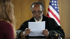 Black male Judge reading a verdict to young woman Stock Footage