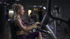 Attractive girl pedaling on the simulator stationary bike at the gym Stock Footage