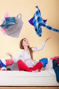 Happy woman on sofa in messy room throwing clothes Kuvituskuvat
