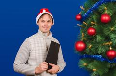 The man with the folder costs near an elegant New Year tree - stock photo