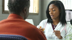 A black female physician prescribing pills to an older black male patient - stock footage