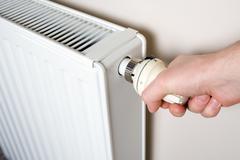 Thermostat adjustment. Men's hand adjusting radiator temperature. - stock photo