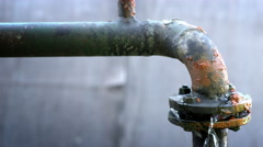 Water leaking from old rusty water supply pipe control valve assembly - stock footage