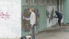 Stock Video Footage of Two male graffiti artists spraying graffiti on wall, street performance, artwork