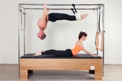 Pilates aerobic instructor woman and man in cadillac fitness exercise - stock photo