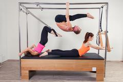 Pilates aerobic instructor a group of three people in cadillac fitness exercise Kuvituskuvat