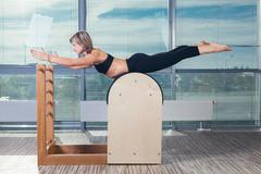 Pilates, fitness, sport, training and people concept - smiling woman doing Kuvituskuvat