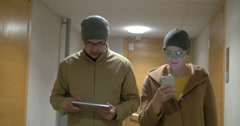 Hipster friends with pad and cell walking in hotel hall Stock Footage