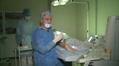 The surgeon conducting the operation to remove veins in the legs. - stock footage