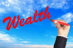 Hand writing word Wealth over blue sky background Stock Photos