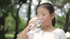 Japanese girl drinking water in a city park Stock Footage