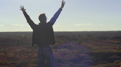 Man Celebrates At An Overlook, He Raises His Arms, Spins Around, Shouts Stock Footage
