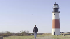 Man Walks, Back To Camera, Toward Historic New England Lighthouse Stock Footage