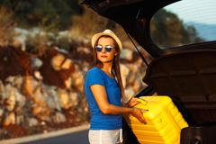 Young woman loading luggage into the back of car - stock photo