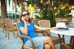 Young modern business woman talking on the phone in a cafe Stock Photos
