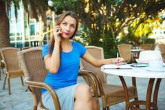 Candid image of a young modern business woman talking on the phone and makes - stock photo