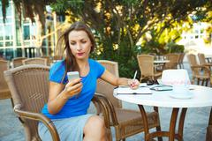 Stock Photo of Candid image of a young pretty modern blogger using smartphone and makes note