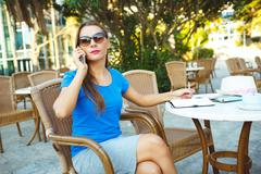 Stock Photo of Candid image of a young modern business woman talking on the phone and makes