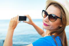 Girl in hat making photos of the Adriatic sea by the smartphone Stock Photos