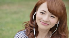 Young attractive Japanese woman listening to music in a city park Stock Footage