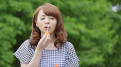 Young attractive Japanese woman blowing soap bubbles in a city park Stock Footage