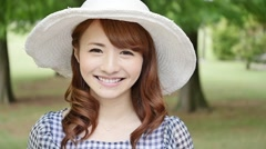 Portrait of young attractive Japanese woman in a city park Stock Footage