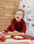 Cute happy little baby girl with big blue eyes in red dress making cookies fo Stock Photos