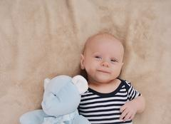 Happy newborn boy with toy wearing in stripped clothing Kuvituskuvat