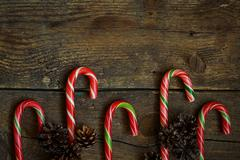 Christmas border with cones and candy cane on wooden boards - stock photo