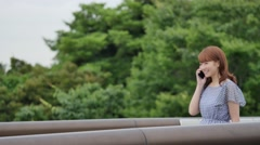 Young attractive Japanese woman  on the phone in a city park Stock Footage