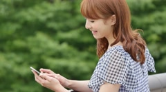 Young attractive Japanese woman with smartphone in a city park Stock Footage