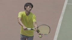 Young Japanese male tennis player in action on the court Stock Footage