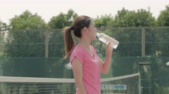 Young Japanese female tennis player drinking water on the court Stock Footage