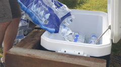 Stock Video Footage of Placing water bottles in a cooler