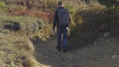 Man Hikes Downhill Carefully - stock footage