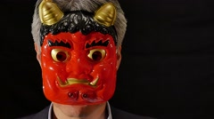 Portrait of senior Japanese man in a suit wearing demon mask - stock footage