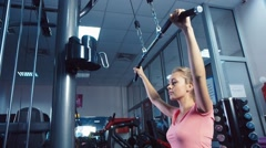 An attractive girl on the simulator training in the gym Stock Footage