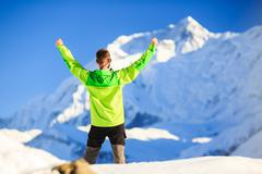 Man hiker or climber achievement in winter mountains - stock photo