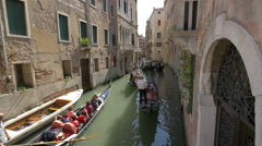Gondoliers rowing gondolas in a small canal in Venice Stock Footage