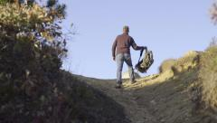 Man Hikes Uphill, Puts His Backpack Down At Top And Raises His Arms Up Stock Footage
