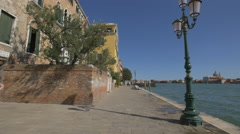 Brick fence and yellow building on the Venetian Lagoon's shore, Venice Stock Footage