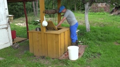 Villager man draw water from well house and pour it to bucket. 4K Stock Footage