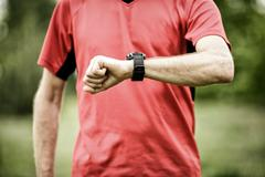 Runner looking at sport or smart watch checking pulse or gps Stock Photos